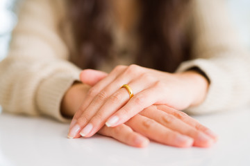 Close up of woman hands on each other wearing a golden alliance for marriage