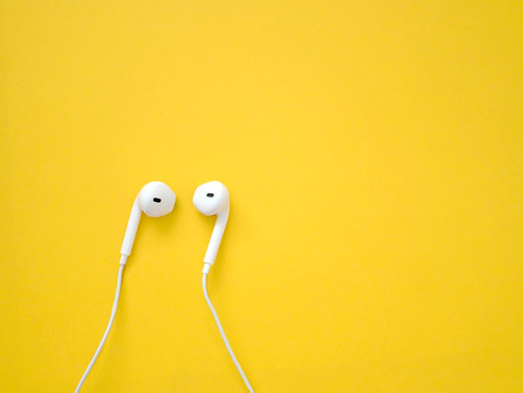 White earphones on yellow background. Earphones for listening to music and sound on portable devices.
