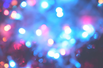 Christmas colorful New Year's Bokeh neon lights. Abstract Blurred photo background with blinking lights from tangled garlands. Decoration with bright colored neon pink blue red green flickering lights