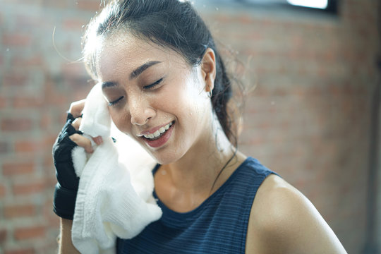 Asian girl exercising in gym she tired and She has sweat on her face.