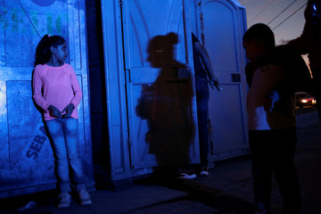 A youth Mexican citizen fleeing violence stands next to temporary toilets as she queues to try to cross into the U.S. to apply for asylum at Cordova-Americas border crossing bridge in Ciudad Juarez
