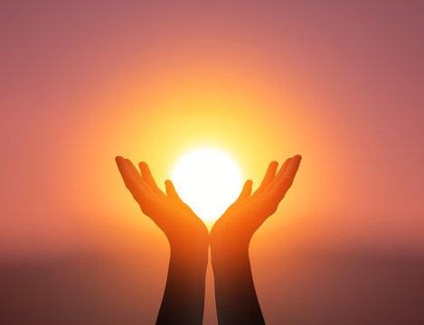 World Mental Health Day concept: Silhouette prayer hands in the sunset sky background