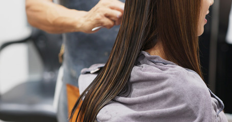 Woman having hair straightening treatment in hair salon