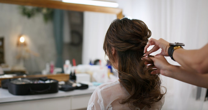 Hairdresser making hairstyle on bride in beauty salon