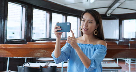 Fotomurales - Woman use of smart phone to take photo on mobile phone and sit on star ferry in Hong Kong