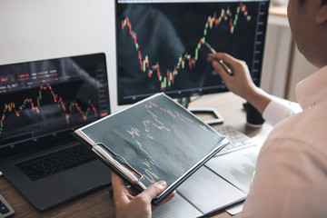 Investor man analyzing the graph of the stock market using a pen pointing to the computer screen.