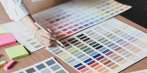 Wall Mural - Young professional UI graphic designer choosing colours for their smartphones templates