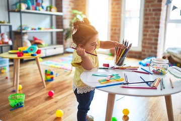 Beautiful toddler standing holding colored pencils at kindergarten