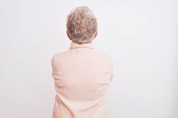 Senior grey-haired woman wearing turtleneck sweater standing over isolated white background standing backwards looking away with crossed arms