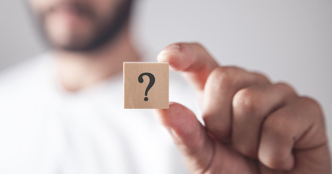 Man showing question mark on wooden cube.