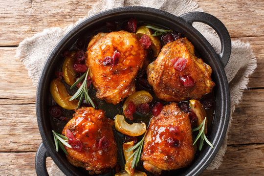 Holiday food hot baked chicken thighs with apples, cranberries and rosemary closeup in a pan. Horizontal top view