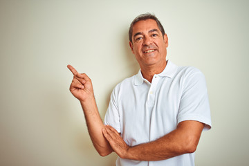 Handsome middle age man wearing polo standing over isolated white background with a big smile on face, pointing with hand and finger to the side looking at the camera. Papier Peint