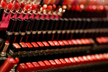 row of lipstick on the table in the shelves of a beauty shop. Probes different cosmetics. Wall mural