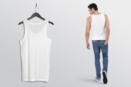 Hanging white plain tank top shirt on wall along with male model in blue denim jeans pant. Rear View. Isolated background