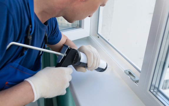 master in protective gloves, seals the cracks of the plastic window with white silicone, close-up