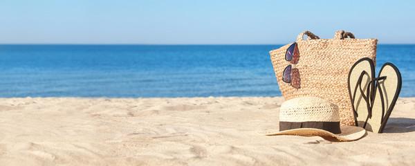 Stylish beach accessories on sandy sea shore. Banner design