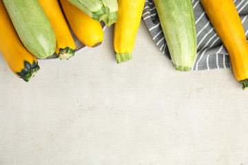 Flat lay composition with fresh ripe zucchinis on light table, space for text