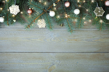 Fir tree branches with Christmas decoration on wooden background, flat lay. Space for text