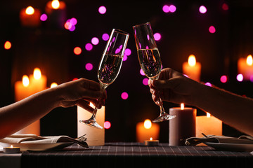 Fototapeta Young couple with glasses of champagne having romantic candlelight dinner at table, closeup obraz