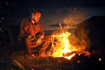 Fotobehang Kamperen Man sitting next to a bonfire in the dark