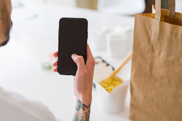 Close upf man using smartphone to orden take away asian food from delivery