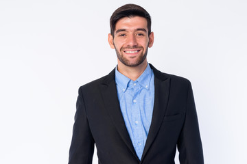 Portrait of happy young bearded Persian businessman in suit smiling