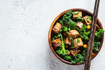 Teriyaki tofu salad with kale and chickpeas in a wooden bowl, copy space, top view.