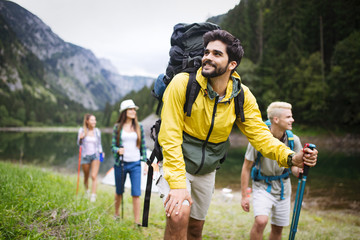 Group of young friends hiking in countryside. Multiracial happy people travelling in nature Wall mural