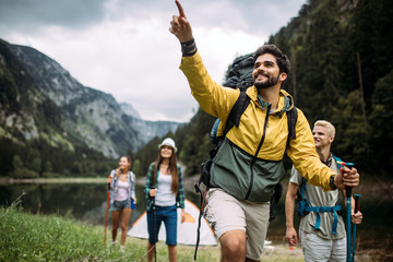 Group of happy friends with backpacks hiking together Fotobehang