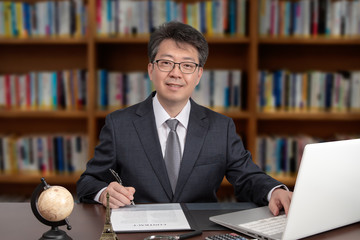 A portrait of an Asian middle-aged male businessman sitting at a desk.