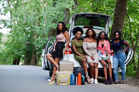Group of five happy african american traveler girls sitting in car open trunk.