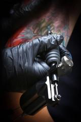 Female tattoo artist making tattoo on a men's arm