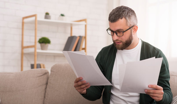 Businessman doing work at home, reading documents