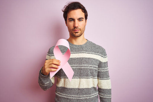 Young handsome man holding cancer ribbon standing over isolated pink background with a confident expression on smart face thinking serious