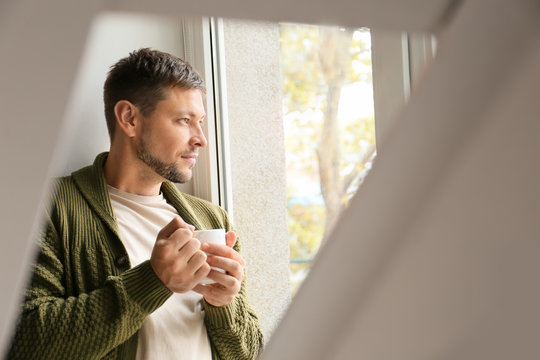Man with cup of tea relaxing near window at home