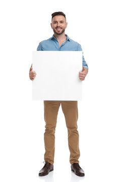 casual man standing with billboard on hands happy