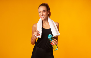 Young Woman Standing Holding Water Bottle And Towel, Yellow Background