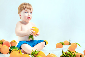 Lovely blue-eyed blond baby sitting in oranges on a light background