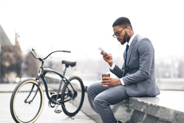 Afro businessman listening music and drinking coffee with bike nearby