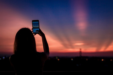 Asian woman taking picture  by mobile phone with sunset sky.