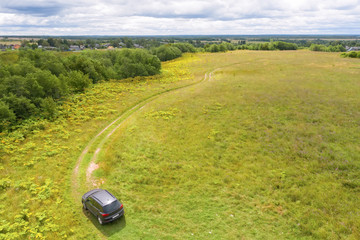 Aerial view on an agricultural field and a car moving on a rut towards the village