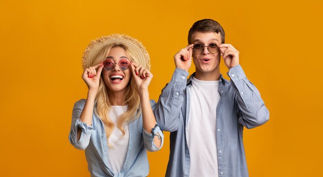 Young couple trying on trendy sunglasses, getting ready for vacation