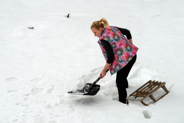 Beautiful girl with a shovel and sled in the snow