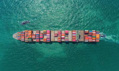 Aerial top view container ship carrier container on the green sea for logistics, import export, shipping or transportation. Wall mural