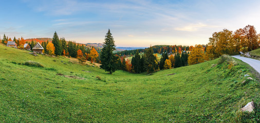 great rural landscape panorama in mountains at dusk. mixed forest on the grassy slopes. old authentic village in the distance. location Ghetari, Alba country, Romania