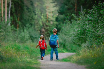 little boy and girl with backpacks going to school, kids walk in nature