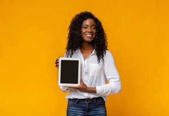 Cheerful black woman demonstrating blank digital tablet screen