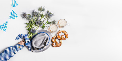 Oktoberfest background .  Mugs of beer, Bavarian hat with feather, pretzel, woman hand in traditional blue blouse and alpin flowers. Top view. Modern. Flat lay. Copy space