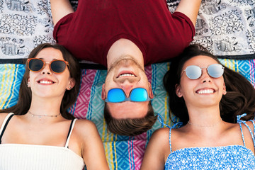 Laughing friends lying together on blanket