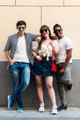 Multiracial trendy people in sunglasses embracing nearby wall